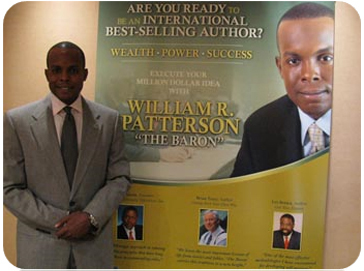 Book Marketing Coach William R. Patterson Standing with Banner